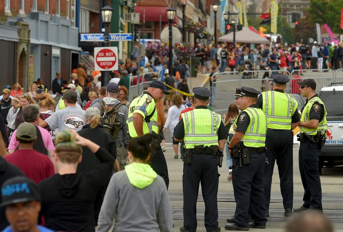 <b></b> New London police officers keep watch over festival-goers from the corner of State and Water streets as thousands gather in downtown New London for the 39th annual Sailfest on July 9, 2016.  As the festival returns this weekend, area police say they're readying for the swell of people and traffic.  (Tim Cook/The Day)