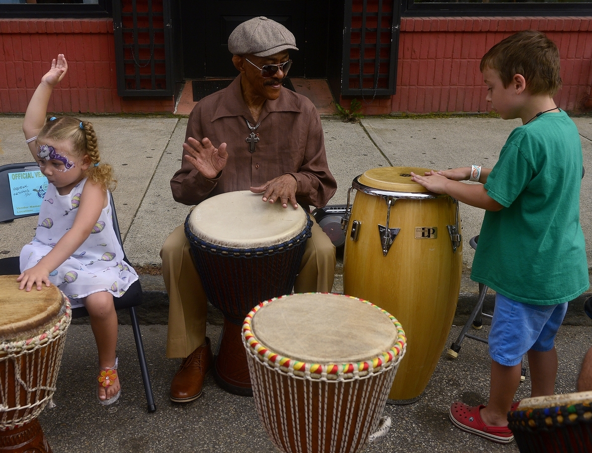 <b></b> Lillian Guess, from left, 3 of New London, plays the drums with Apache, of New York, and Oscar Stallard, 5 of New London, along Bank Street during the final day of Sailfest on Sunday, July 15, 2018 in New London. (Sarah Gordon/The Day)