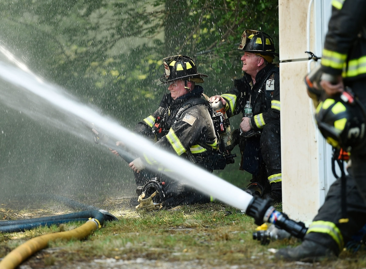 <b></b> Firefighters mount an exterior attack after being called out of the building while battling a house fire at 702 New London Turnpike in Norwich Monday, July 16, 2018. The East Great Plain volunteer fire department was assisted by Mohegan Tribal Fire FAST, Norwich City, Yantic, Mohegan and Montville volunteer departments on the scene. (Sean D. Elliot/The Day)
