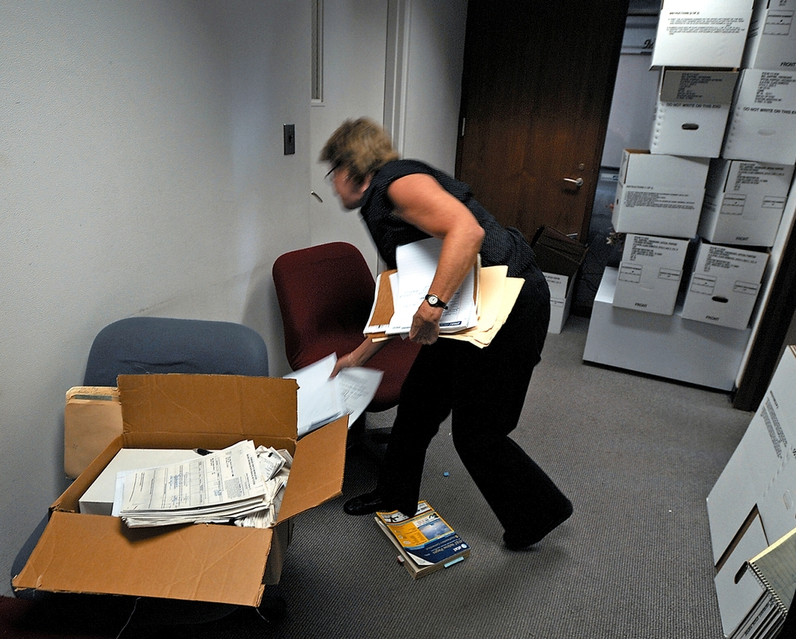 <b></b> An employee of the New London Security Federal Credit Union sorts documents in the hallway of the closed office on July 29, 2008. (Tim Martin/The Day)