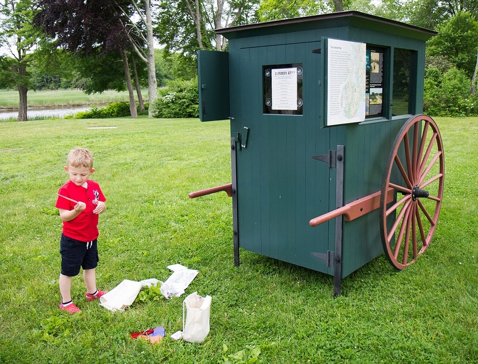 A young visitor checks out one of the Explorer Kits the Art Cart has to offer.