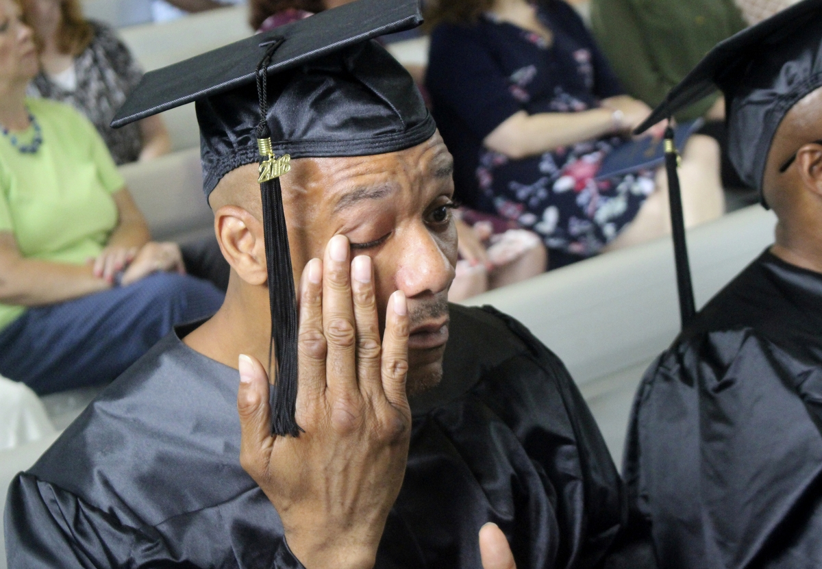 <b></b> Clyde Meikle, who is serving a 50-year sentence for murder, wipes a tear from his eye during graduation ceremonies on Wednesday, Aug. 1, 2018, inside the Cheshire Correctional Institution in Cheshire, Conn. Meikle was among 18 inmates who received an associate degree from Middlesex Community College as part of a program with Wesleyan University's Center for Prison Education. (Pat Eaton-Robb/AP Photo)