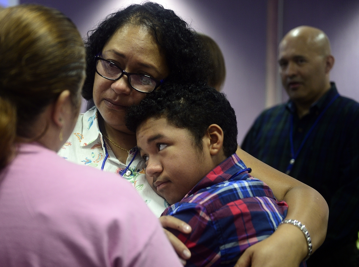 <b></b> Santiago Rodriguez, 14, of New London, hugs his mother, Diana, following a news conference Tuesday, Aug. 14, 2018, regarding the deportation of his father, Julian, back right, at Connecticut Children&#xb4;s Medical Center. Santiago suffers from a rare genetic disease that requires intensive, regular treatment at the center. (Sarah Gordon/The Day)