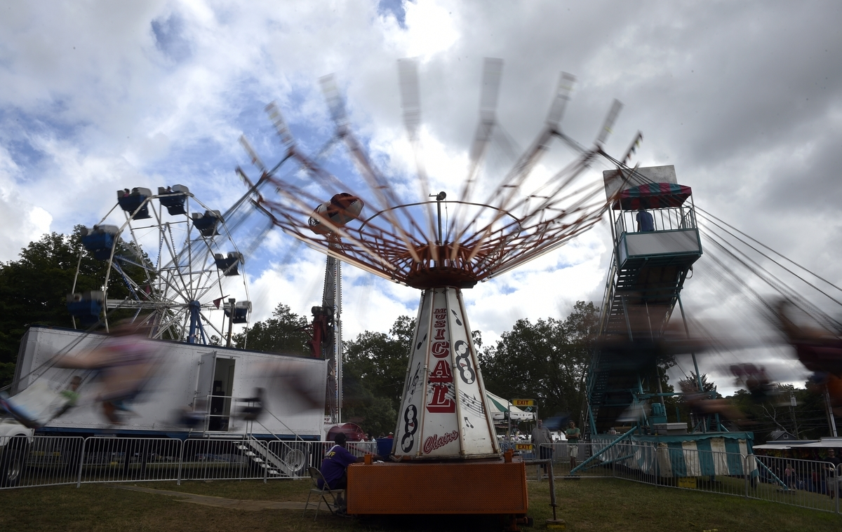 <b></b> Fairgoers ride the Musical Chairs ride of the 114th Hamburg Fair at the Lyme Grange Fair Grounds, Sunday, August 23, 2015. (Tim Martin/The Day)