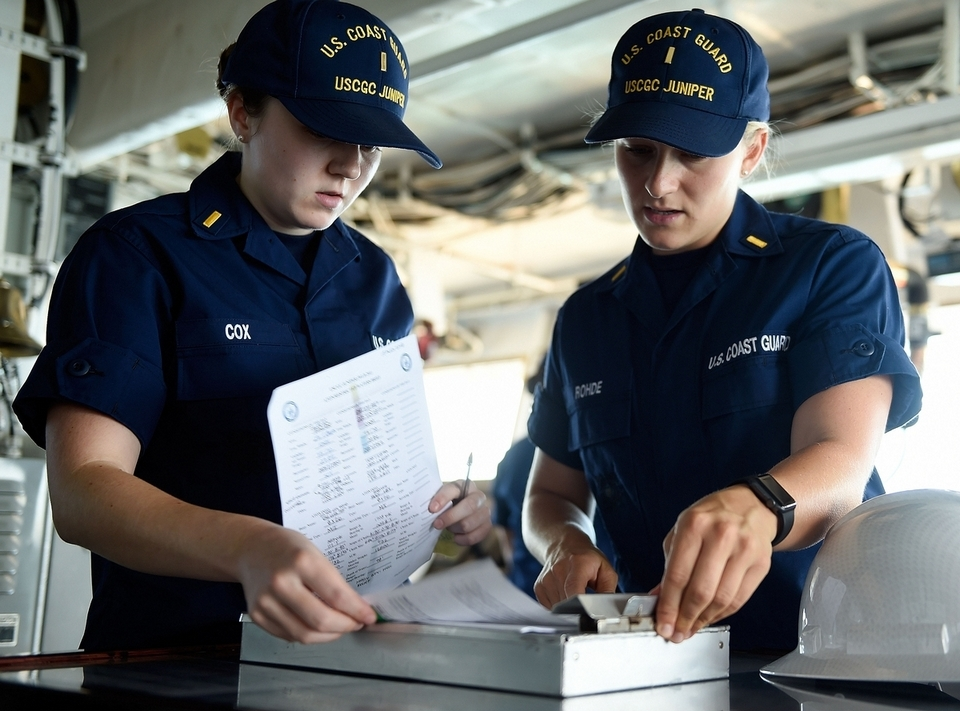 U.S. Coast Guard Ensign Dana Rohde, right, briefs her replacement as operations officer, Ensign Emily Cox, as the cutter Juniper performs aids to navigation maintenance on two buoys Wednesday, Aug. 15, 2018. (Sean D. Elliot/The Day)