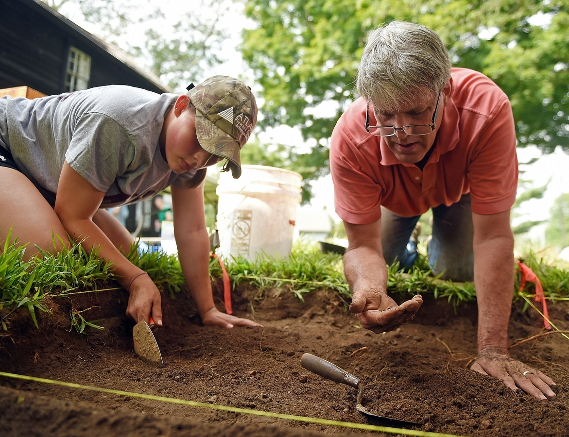 <b></b> Hannah Smith, left, looks for artifacts as her father, Escott, examines a piece of ceramic as they join other volunteers in an archaeological dig program at the East Lyme Historical Society's Thomas Lee House Museum on Friday, Aug. 17, 2018.  (Sean D. Elliot/The Day)