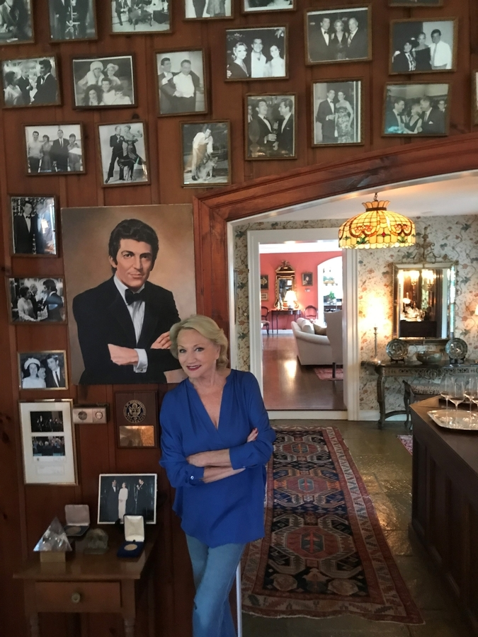 <b></b> Eva Franchi poses in front of a portrait of her late husband, Sergio Franchi, on Aug. 22, 2018, in the music room of their Stonington estate. (David Collins/The Day)