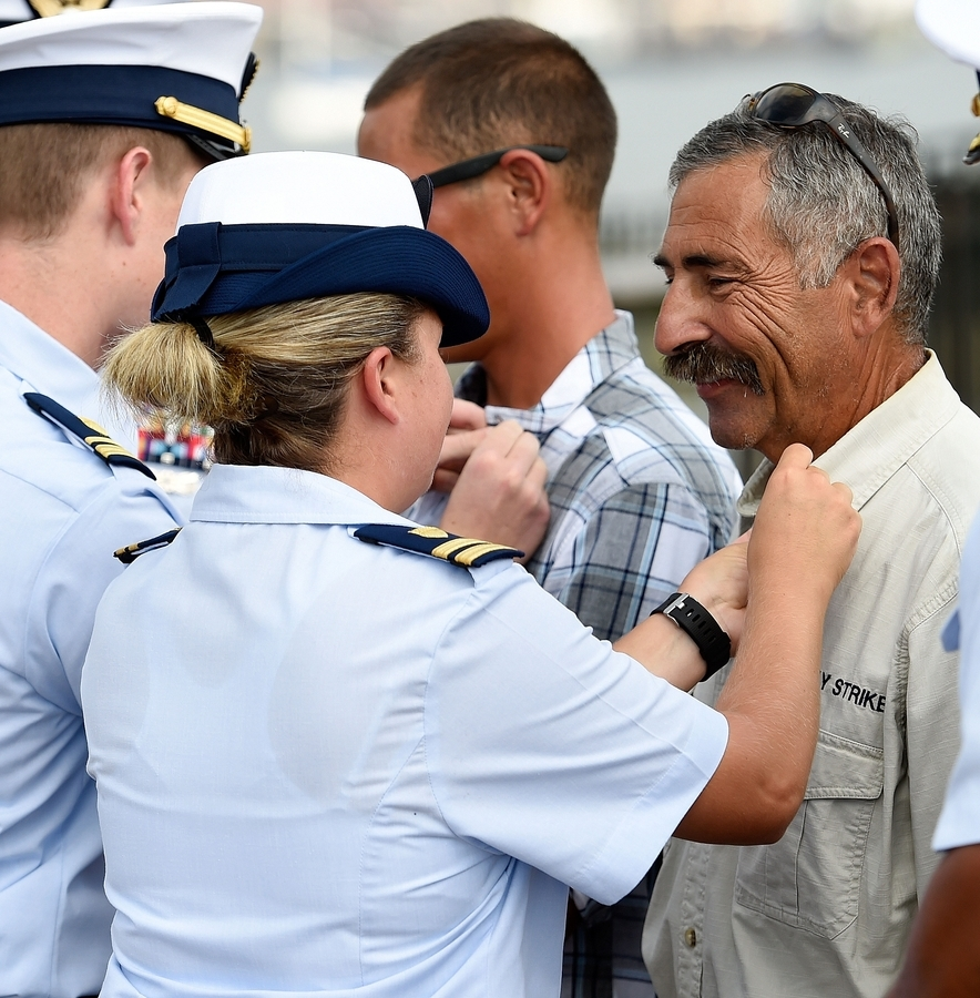 Marc Berger, right, captain of the charter fishing vessel Lucky Strike, and his son and first mate, Michael Berger, center, are presented with pins honoring them for a rescue of four boaters from the waters off Niantic in July by Lt. Nina McDonald, commander of Coast Guard Station New London, second from left, and Lt. j.g. Brandon Newman, commander of the Coast Guard Cutter Albacore, left, during the kickoff ceremony for the sixth annual Connecticut Maritime Heritage Festival on Thursday, Sept. 6, 2018, at Fort Trumbull State Park in New London.  (Sean D. Elliot/The Day)