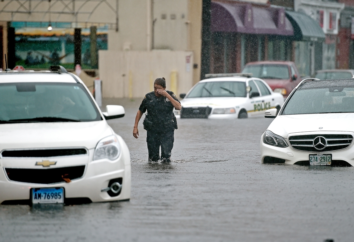 <b></b> New London police Officer Deana Nott walks back to dry land after talking to motorists stranded in their cars due to flooding on Bank Street in New London during torrential rains Wednesday, Sept. 12, 2018. (Sean D. Elliot/The Day)