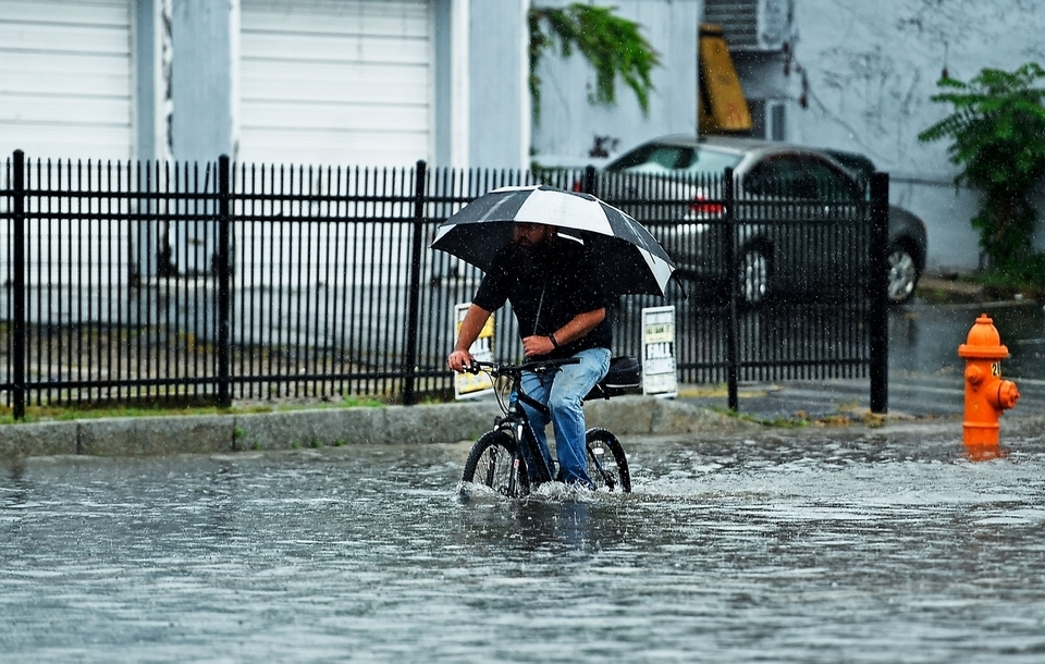 A cyclist makes his way through floodwaters on Bank Street in New London due to torrential rains Wednesday, Sept. 12, 2018. (Sean D. Elliot/The Day)