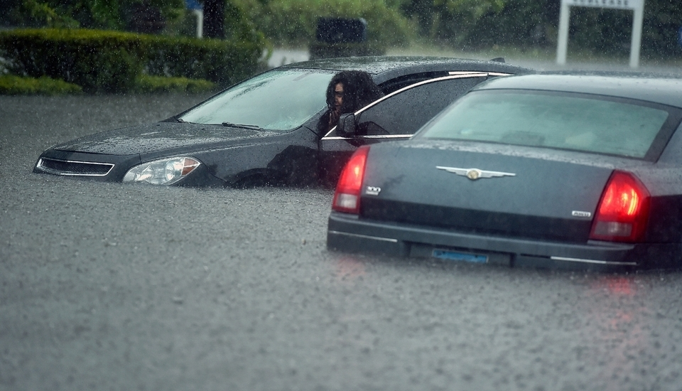 Tiara Corley of New London pushes her stranded vehicle along Broad Street near Connecticut Avenue as torrential rains flood  the area near Ledyard Street on Wednesday, Sept. 12, 2018, in New London. (Tim Martin/The Day)