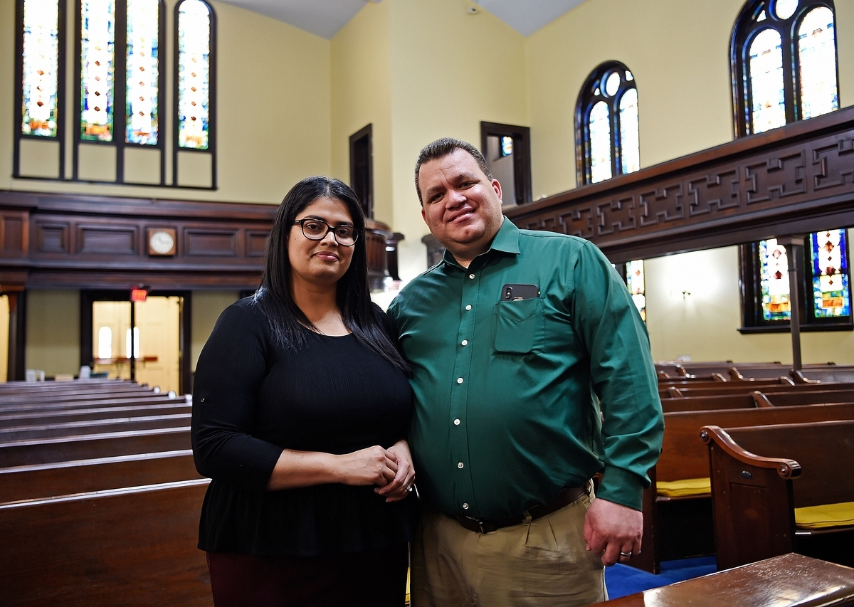 <b></b> Jonathan Quinones, pastor of United Congregational Church, and his wife, Gloria, stand in the Norwich church's sanctuary Thursday, Sept. 13, 2018. United Congregational will celebrate its centennial this Saturday. (Sean D. Elliot/The Day)
