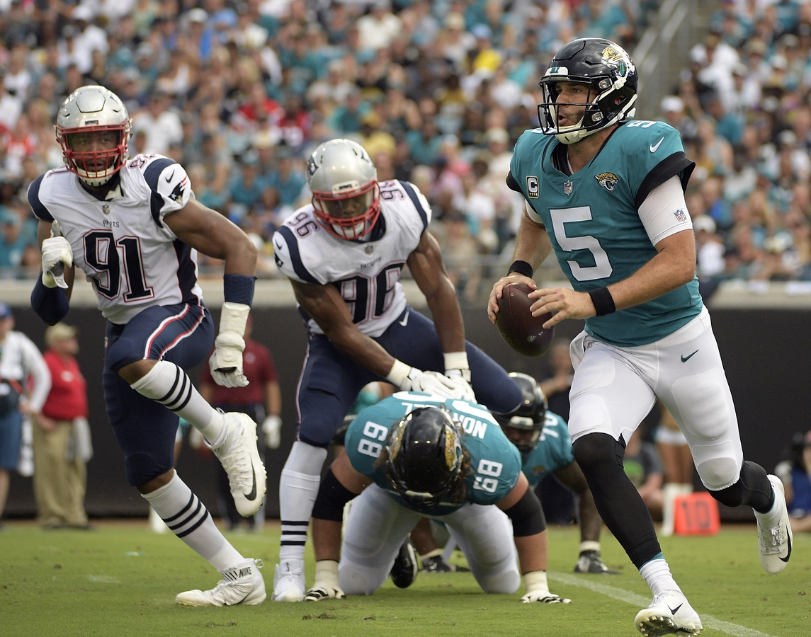 <b></b> Jacksonville Jaguars quarterback Blake Bortles (5) scrambles as he is pressured by New England Patriots defensive ends Deatrich Wise (91) and Geneo Grissom (96) during the first half of Sunday's game at Jacksonville, Fla. (AP Photo/Phelan M. Ebenhack)