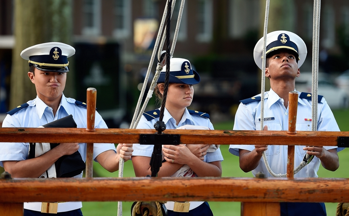 <b></b> Members of the cadet morning colors detail at the U.S. Coast Guard Academy, from left to right, Cadet Fourth Class Andrew Suh, Cadet Third Class Katie Schiavo, and Cadet Fourth Class Garrett Drummond, prepare the halyards for the POW MIA and Coast Guard flags for the start of a new week Monday, September 17, 2018.   Morning colors takes place daily at the academy at 8 a.m. with the sounding of a bugle and the ringing of the chapel bells. Evening colors takes place at sunset each day. (Sean D. Elliot/The Day)