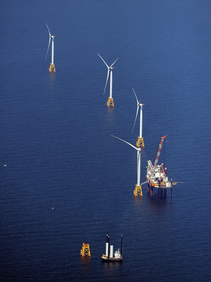 Workers on the jack-up construction vessels Brave Tern and L/B Caitlin prepare to install the final blade on the the fourth of the five power generating wind turbines as part of the Deepwater Wind project three miles south of Block Island on Aug. 15, 2016. Deepwater is among wind energy producers competing in Connecticut's new zero-carbon energy auction. (Sean D. Elliot/The Day)