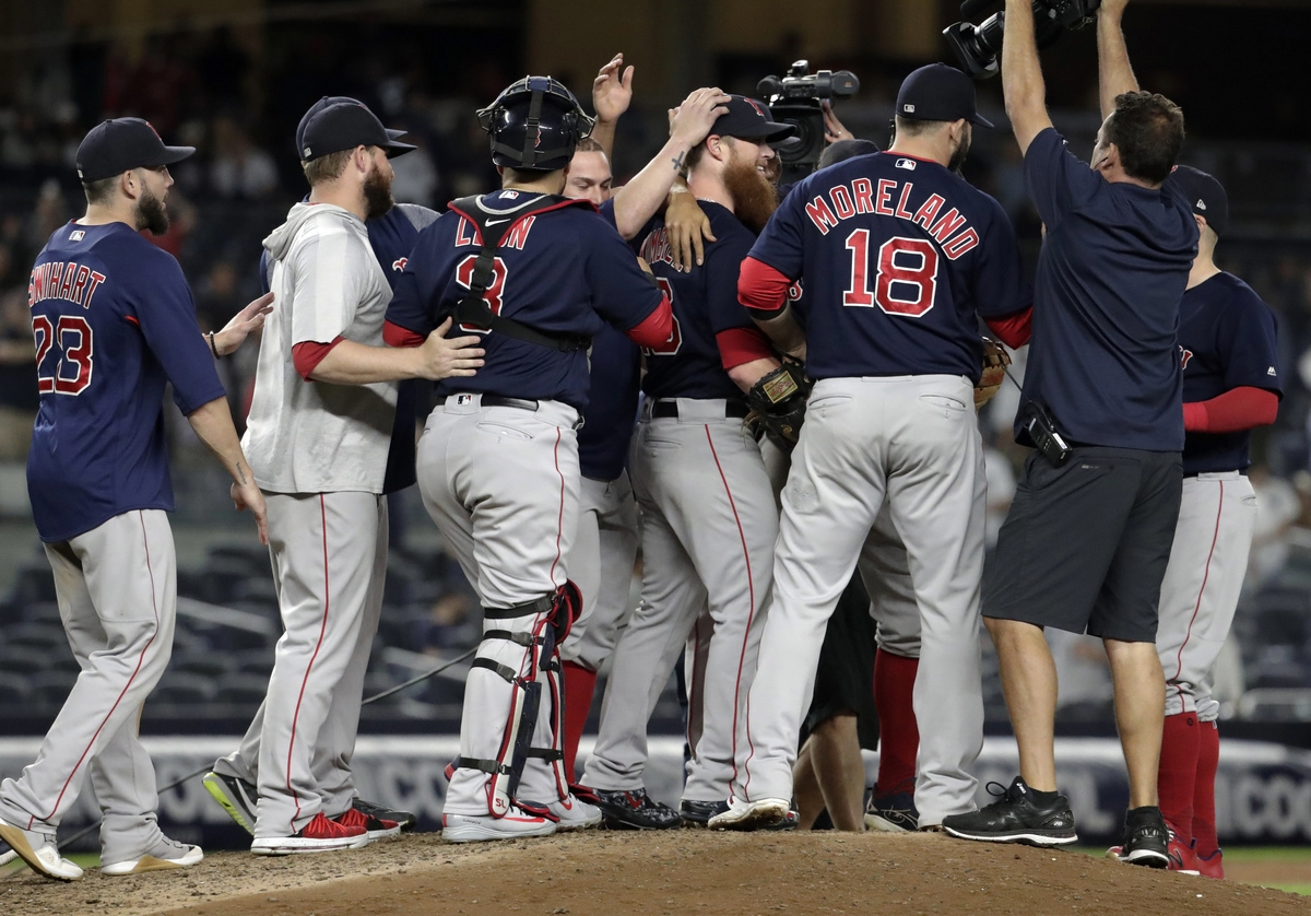 <b></b> Red Sox players surround relief pitcher Craig Kimbrel, center, after they defeated the New York Yankees 11-6 on Thursday night in the Bronx to clinch their third straight American League East title. (AP Photo/Julio Cortez)