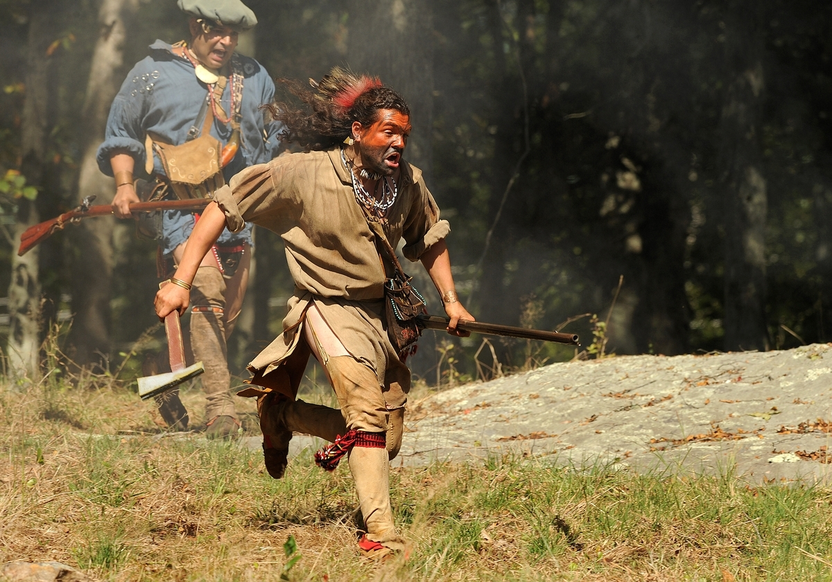 <b></b> Drew Shuptar-Rayvis, right, of New Milford, a member of the Schaghticoke First Nation tribe portraying a Mahican tribe warrior, and Dan Bosques left, of Ansonia, a member of the Taino Tribe portraying a Paugussett tribe warrior, run toward a militiaman during a skirmish while participating in the King Philip's War reenactment at the Denison Homestead in Mystic on Oct. 1, 2017.  The event returns to the homestead this weekend. (Dana Jensen/The Day)