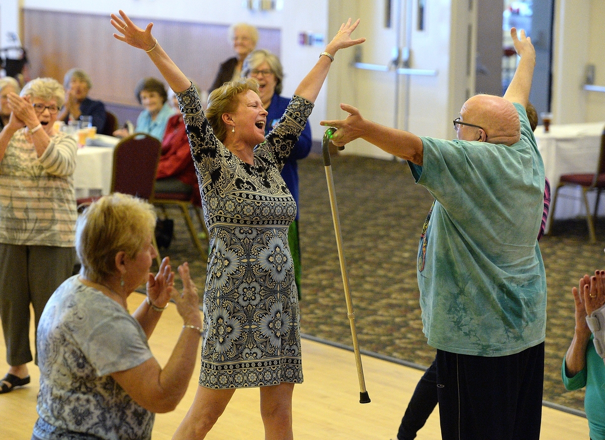 <b></b> Cathy Wilson, center, director of the East Lyme Senior Center, dances and sings with a member of the Senior Center while attending the Under the Sea Senior Prom at the Port 'N Starboard at Ocean Beach Park in New London on Friday, Oct. 5, 2018. The annual event is presented by The Senior Centers of Southeastern CT. It featured a sit-down dinner and entertainment by Jose Paulo, who offered music and dance lessons.   (Dana Jensen/The Day)