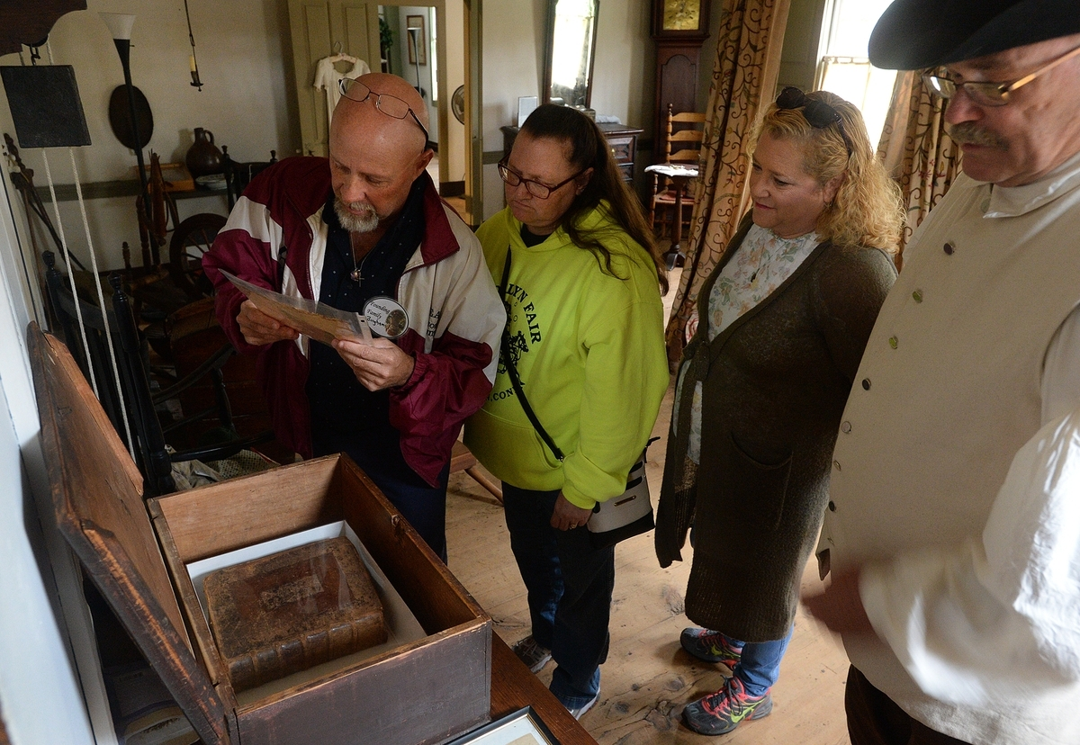 <b></b> Michael Passmore, left, of Ballouville, his twin sister, Michelle House of Dayville, both descendants of the Leffingwell, Bingham and Backus families of Norwich, and Sandy Kirca of Ballouville look at the list of names that appear in the Leffingwell family Bible that is in the box, while docent Dennis Guillemette, right, gives them a tour of the Leffingwell House during the Founders's Day celebration at the museum in Norwich on Saturday, Oct. 6, 2018.   (Dana Jensen/The Day)