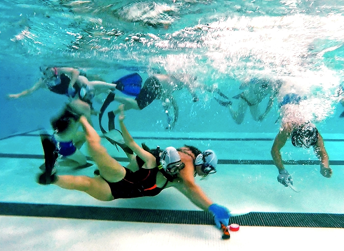 <b></b> Players fight for control of the puck during an underwater hockey game Aug. 19, 2018, in the pool at the University of Connecticut's Avery Point campus in Groton. (Sarah Gordon/The Day)