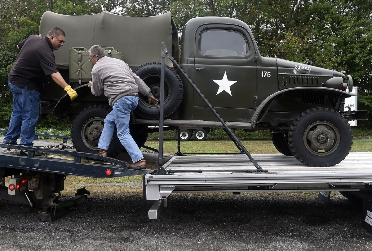 <b></b> Robert Cade, with Medallion Transport, left,  gets some help from Dan Caldwell as he a 1945 WC-12  onto a trailer at the Ledyard Fairgrounds on Monday, October 8, 2018. The truck has been in Debby Caldwell's, Dan's wife,  family for over 70 years and is making it's way to the National Museum of the United States Army. (Sarah Gordon/The Day)