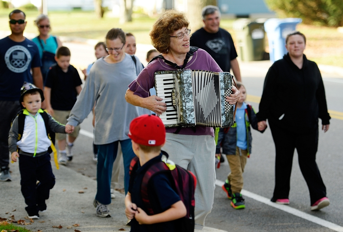 <b></b> Roz Etra, a retired music educator and neighbor, plays her accordion as students and staff from the Stanton Network School in Norwich walk along New London Turnpike on Wednesday, Oct. 10, 2018, for their third annual Walk to School Day.  (Sean D. Elliot/The Day)