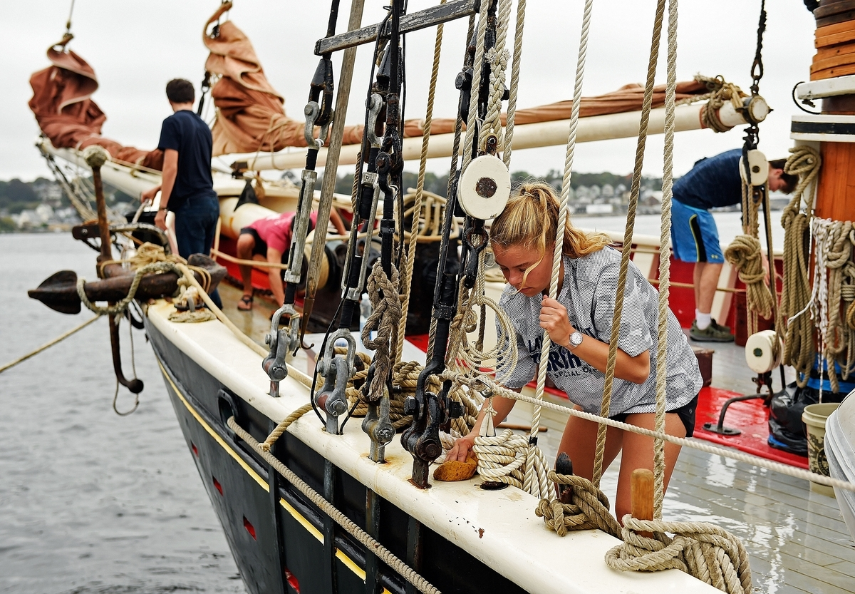 <b></b> P.J. Shaw, 16, from Sunapee, N.H., scrubs the rail as crew and students aboard the schooner Roseway clean the vessel as part of a