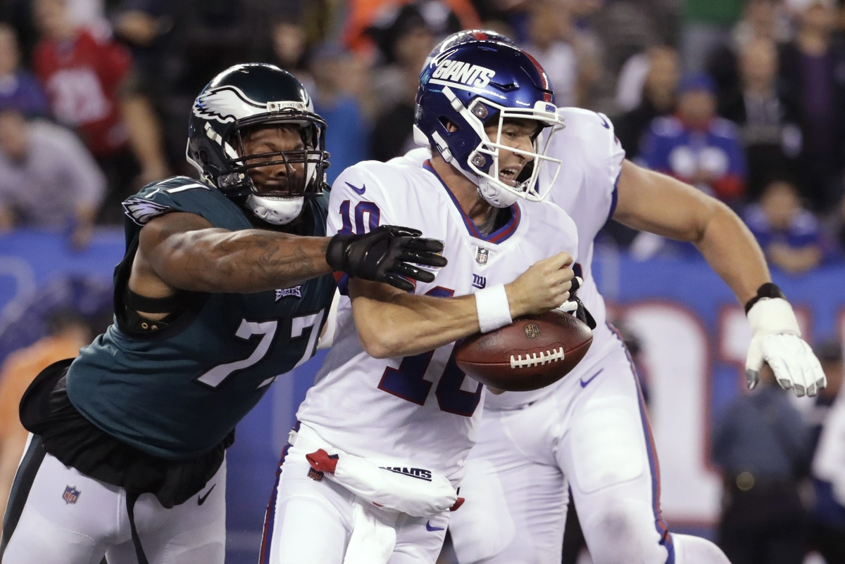 <b></b> Philadelphia defensive end Michael Bennett (77) strips the ball from Giants quarterback Eli Manning during the first half of Thursday night's game at MetLife Stadium, where the Eagles routed the Giants 34-14. (AP Photo/Julio Cortez)