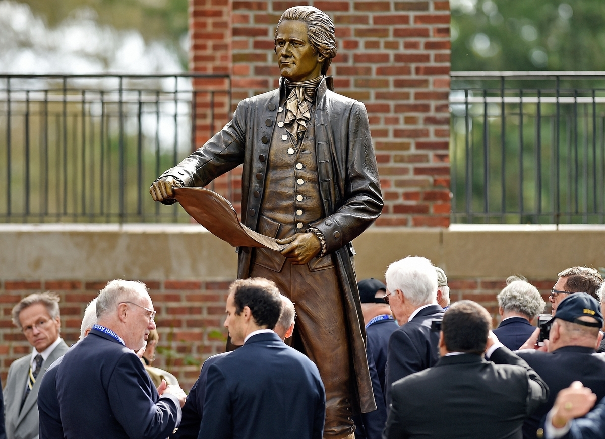 <b></b> Members of the U.S. Coast Guard Academy Class of 1963 move in for a closer look at their gift to the academy, a statue of Coast Guard founder Alexander Hamilton, on Friday, Oct. 12, 2018, in front of Hamilton Hall at the academy in New London, Conn.  (Sean D. Elliot/The Day)
