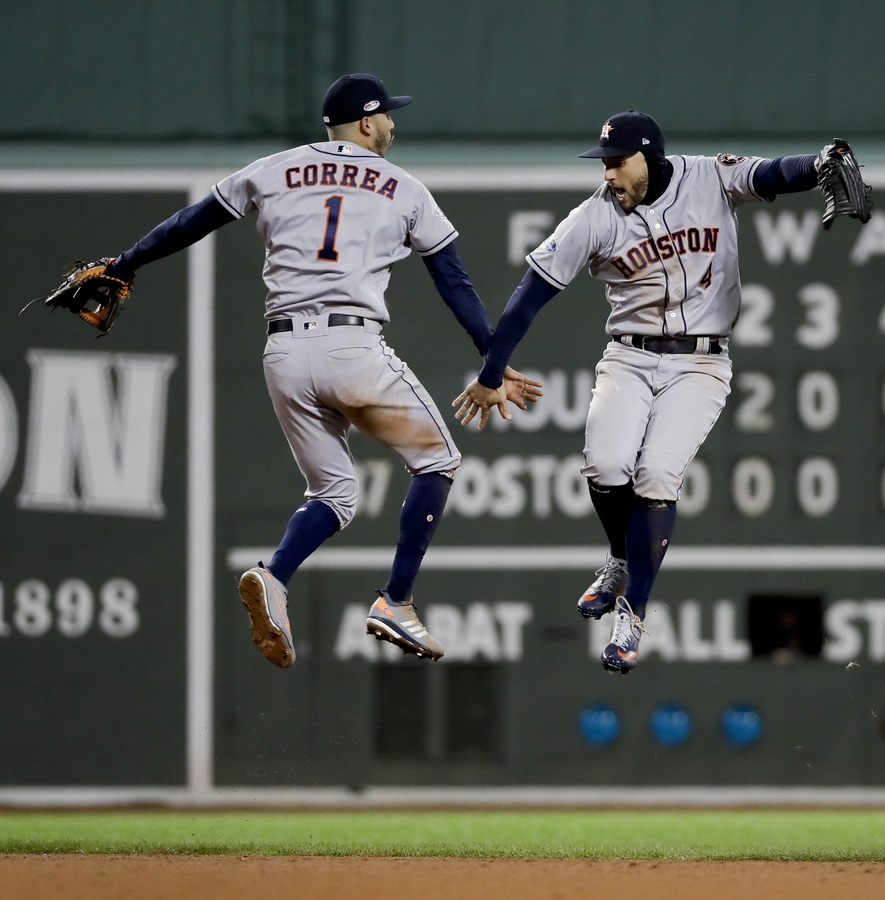 <b></b> Houston center fielder George Springer, right, and shortstop Carlos Correa celebrate the Astros' 7-2 win over the Red Sox in Game 1 of the American League Championship Series on Saturday night at Fenway Park in Boston. (AP Photo/David J. Phillip)
