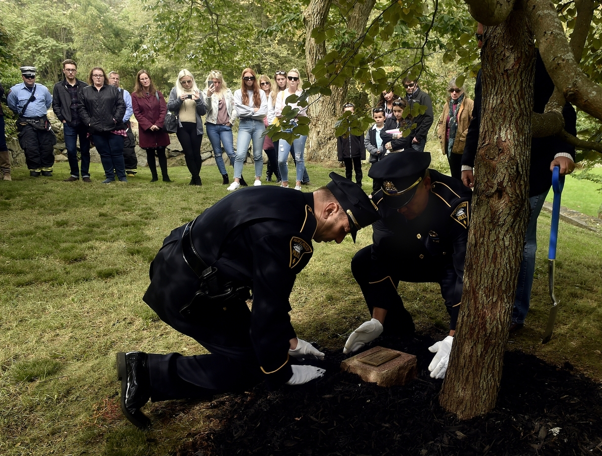 <b></b> New London Police Lieutenant Robert Pickett, from left, and Officer Richard Cable place a memorial stone honoring Juliana McCourt during a re-dedication ceremony at Lyman Allyn's McCourt 9/11 Memorial Garden on Sunday, October 14, 2018. New London resident Juliana, four years old, and her mother Ruth were on Flight 175 and victims of the 9/11 terrorist attacks.  The memorial stone was previously installed on the campus of Mitchell College where Juliana was a student at the Children's Learning Center. (Sarah Gordon / The Day)