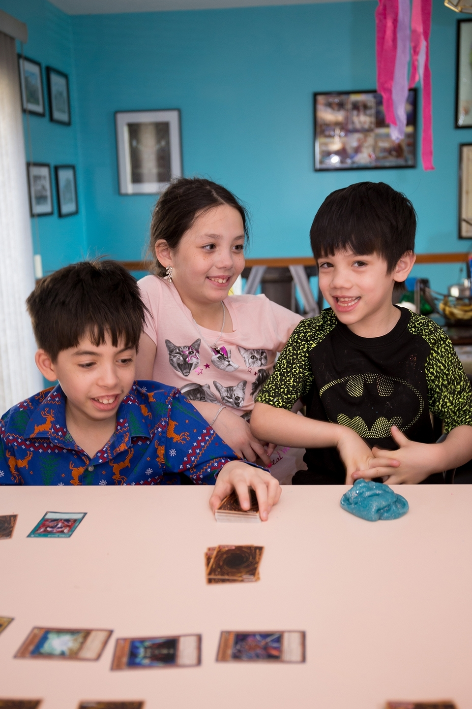 Brady, 11, Prudence, 10, and Caleb, 6, play Yu-Gi-Oh! on a recent morning at home in Montville. (Renee Trafford photo)