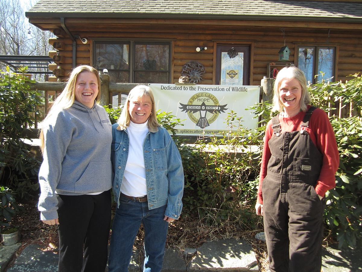 Wildlife rehabilitator Christine Cummings (right), owner of A Place Called Hope, stands in front of the sign for her rehabilitation center with rehabilitators Amanda Morgillo (left) and Vickie Silvia. (Photo by Todd McLeish)
