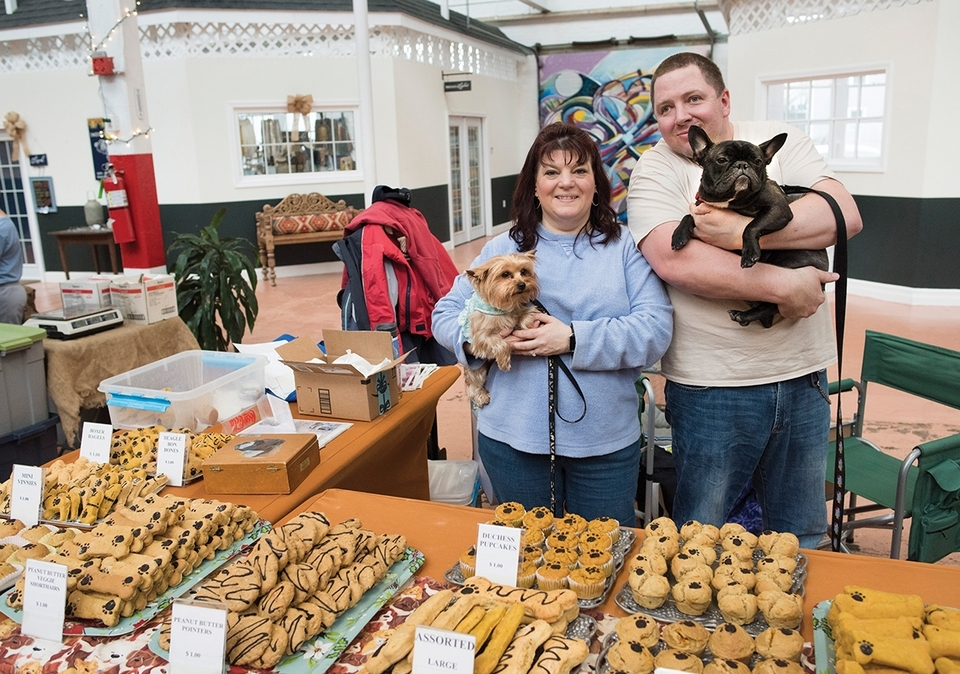 Pam and Justin Nyack (holding Pebbles and Vinnie) of Duchess Pet Treats take part in the Saturday Farmers Market at the Velvet Mill in Stonington. (Peter M. Weber photo)